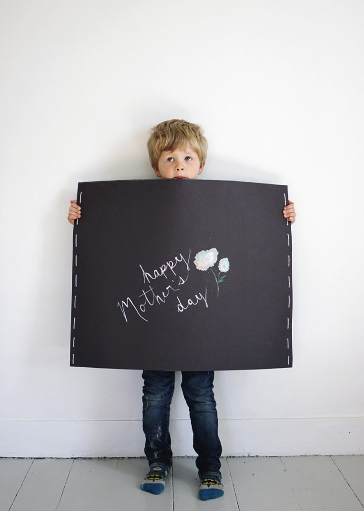 A boy holding an illustration board with a written greetings for mother's day.