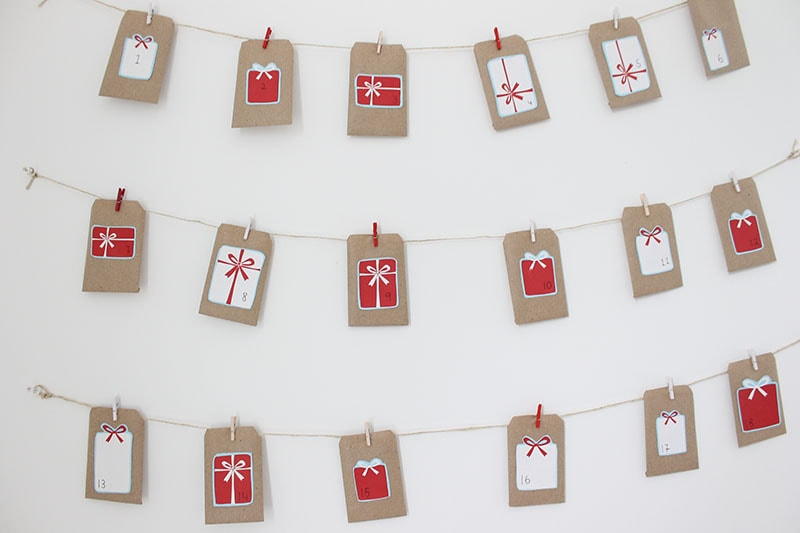 DIY paper gift tag on strings pinned on white wall