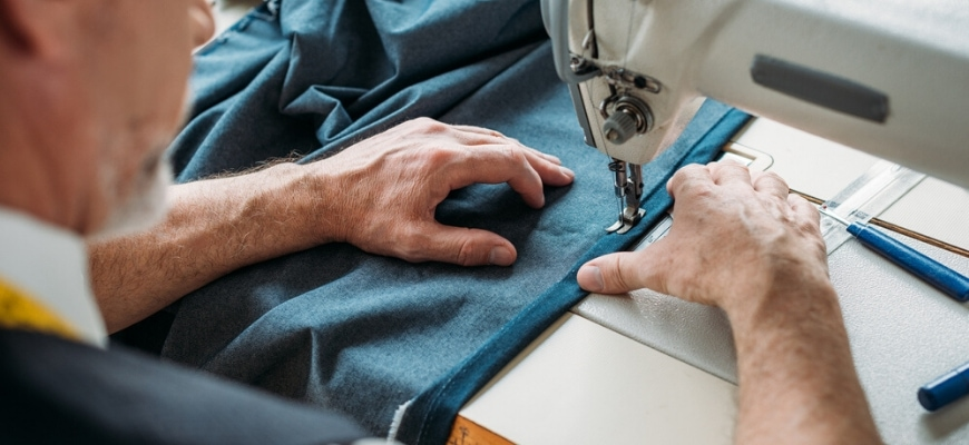 An old man hemming a jean on a sewing machine