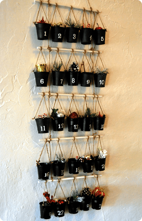 Small black pots tied in stick hang on a white wall