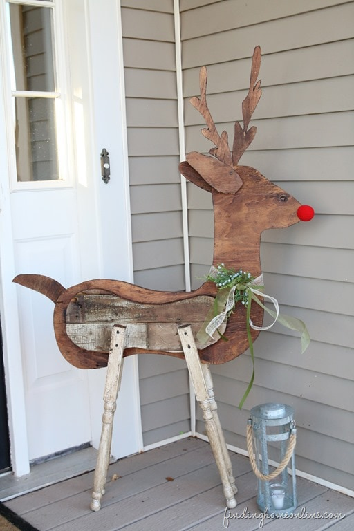 DIY reclaimed wood reindeer besides a tin lantern
