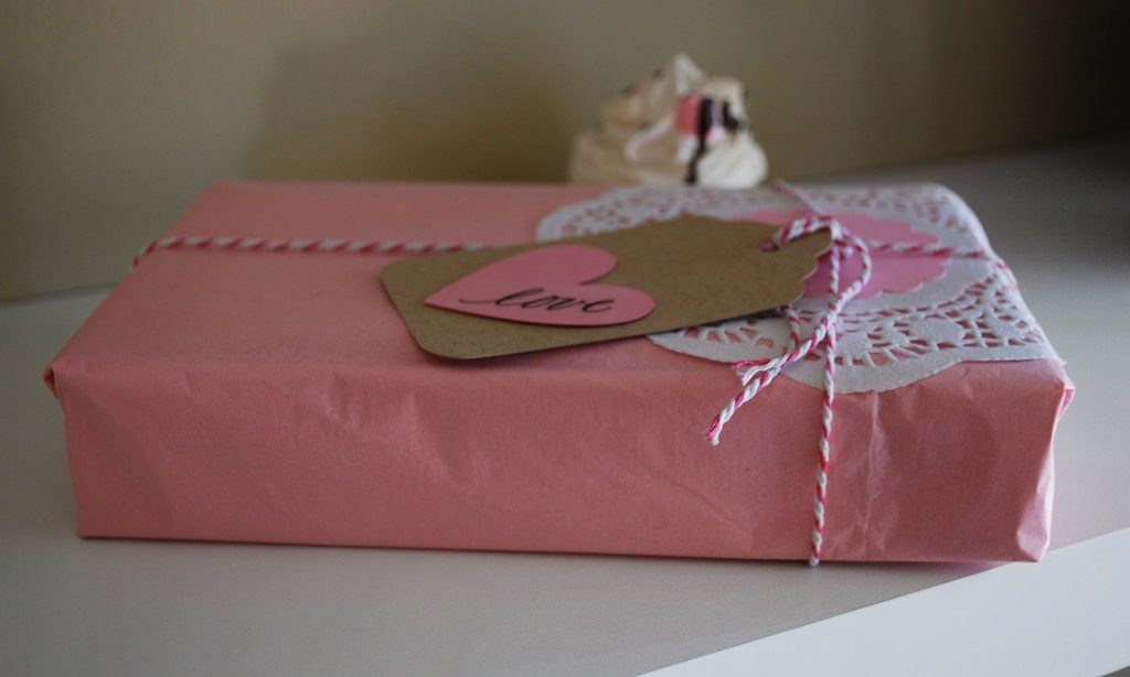 Pink wrapping paper with white and pink string and brown tag with pink heart with love note