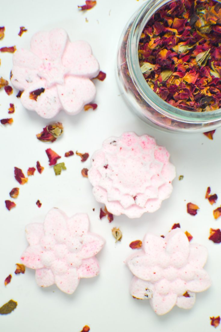 DIY floral bath bombs with a jar of dried leaves on the side.