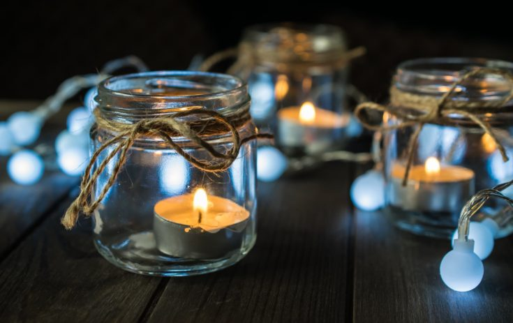 Decorative dark and moody composition with mason jar candles and lights on wooden table