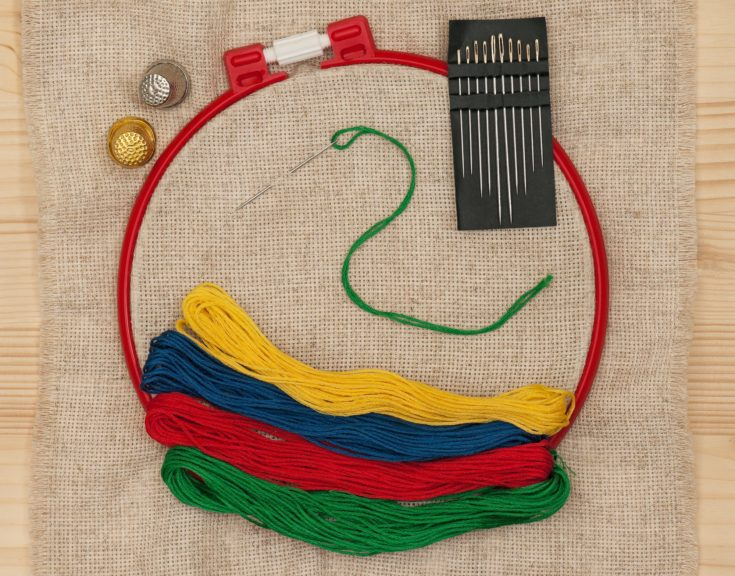Bright embroidery accessories with sewing needles over outline background