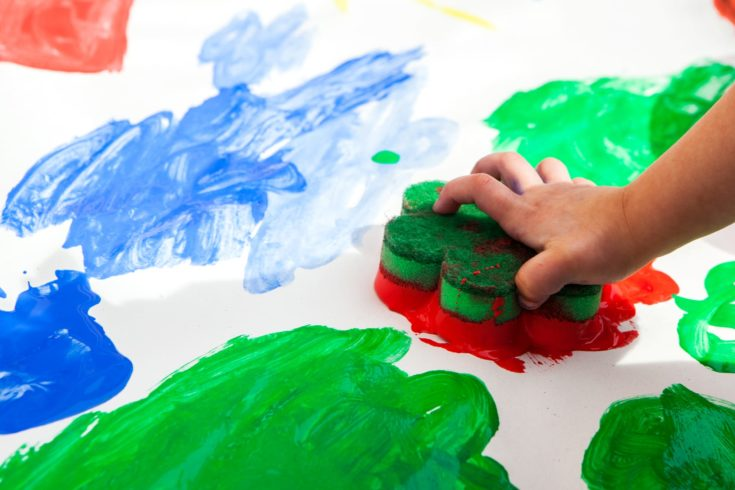 Child hand painting red colour on paper