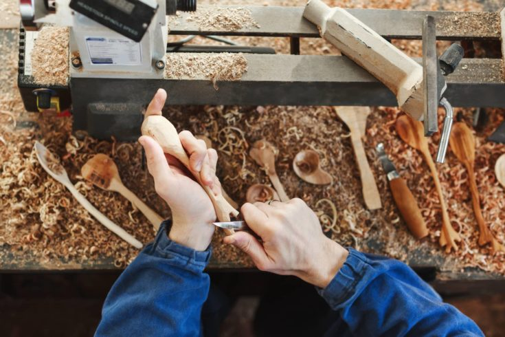 Man's hands in blue jeans working suit carving a wooden spoon with a knife, wooden shavings, spoons and instruments on table at background, close up, woodworking.