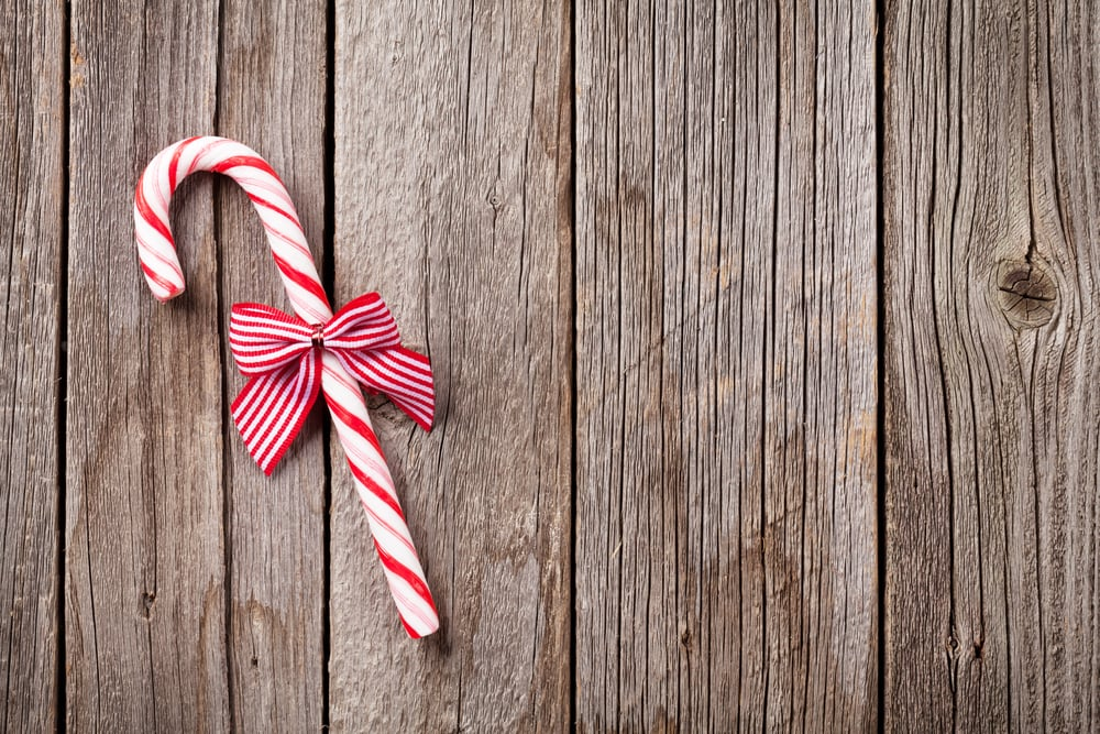 Christmas candy cane on wooden table. Top view with copy space