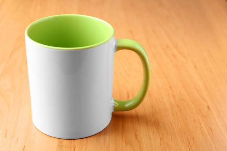 White with green mug for branding on wooden table