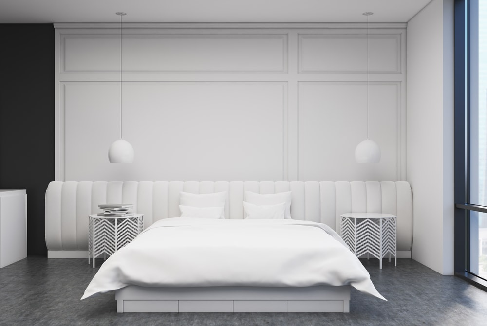 White bedroom interior with a concrete floor, a large bed with a white cover and two bedside tables. 3d rendering mock up