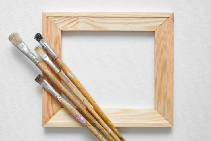 Wooden stretcher bar and paintbrushes on white artist canvas background. Top view. Copy space for text.