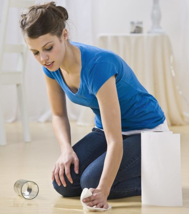 An attractive young woman cleaning up a spilled glass of water in her home. She is using paper towels and is cleaning a hardwood floor. Vertically framed shot.