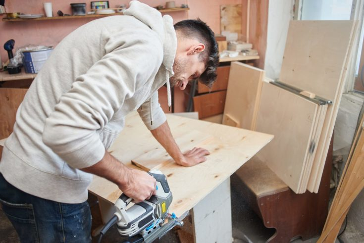 Young man working with electric fretsaw while sawing plywood,