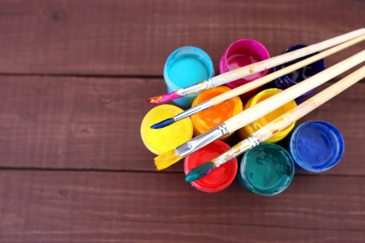 Colorful acrylic paints with paint brushes on wooden background