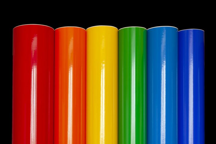 Rolls of colored vinyl film isolated on a black background.