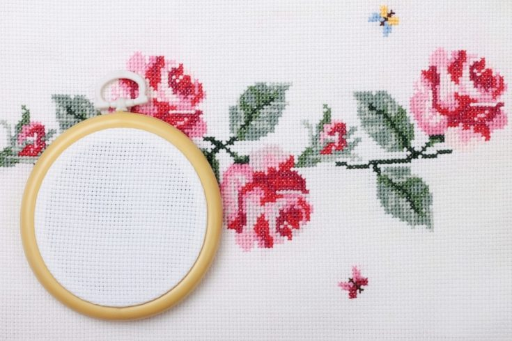 background with embroidered cross on canvas patterns of flowers roses