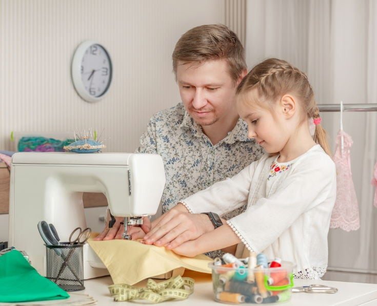 cute little girl and her dad in a sewing workshop