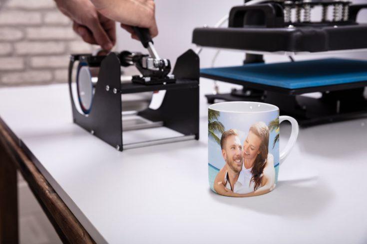 Man printing on coffee mugs in workshop
