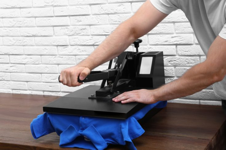 Man using heat press machine at table near white brick wall, closeup