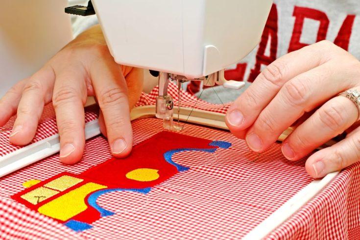 Woman operating embroidery machine.