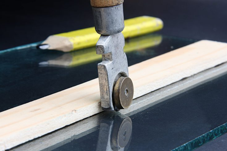 Glass cutter on the background of window glass and pencil.