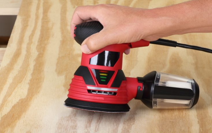 Electric circular sander sanding a piece of plywood