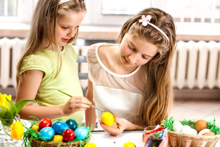 Happy children paint Easter eggs at home.