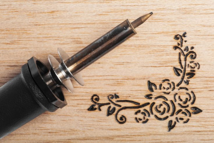A pyrography tool and a floral model.