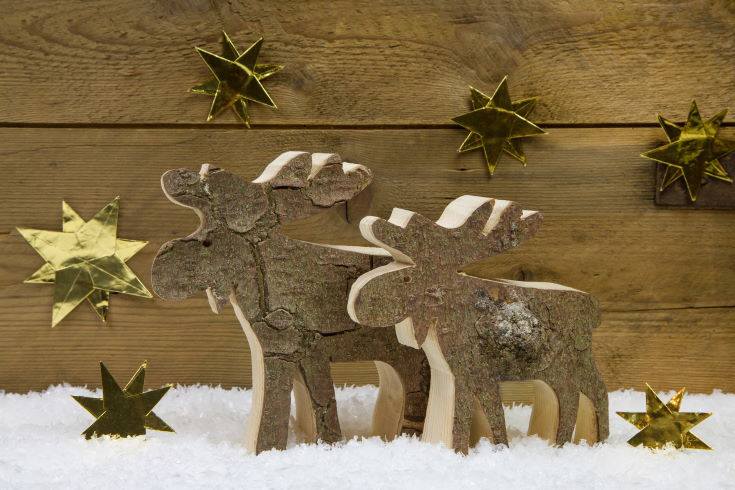 Two wooden handmade reindeer for christmas decoration with natural materials. Also with golden stars on the wooden background.