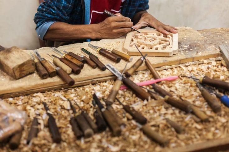 Carver in wood working in workshop, India