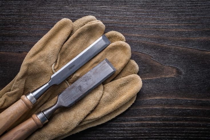 Pair of brown leather gloves with firmer chisels on vintage wooden board construction concept.