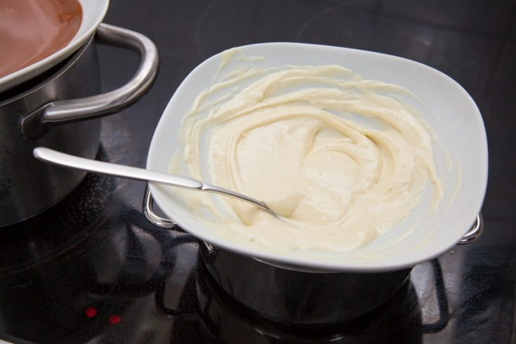 White chocolate couverture in a water bath on a stove with spoon.