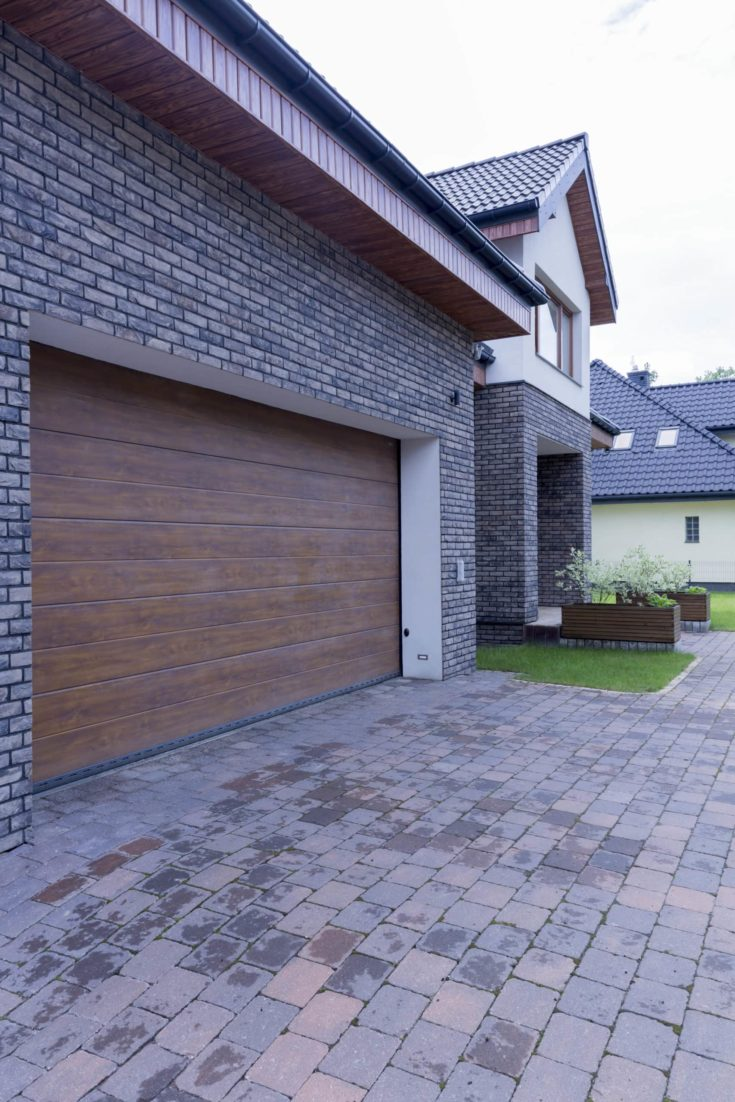 Front of modern detached house with automatic garage door and driveway