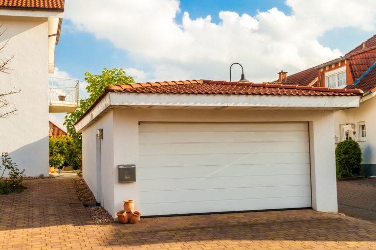 Detached white garage with orange brick tile roof