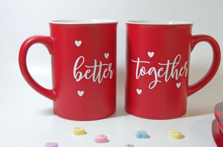 Printed couple red mugs and heart shapes beads spread in front of it in a white background.