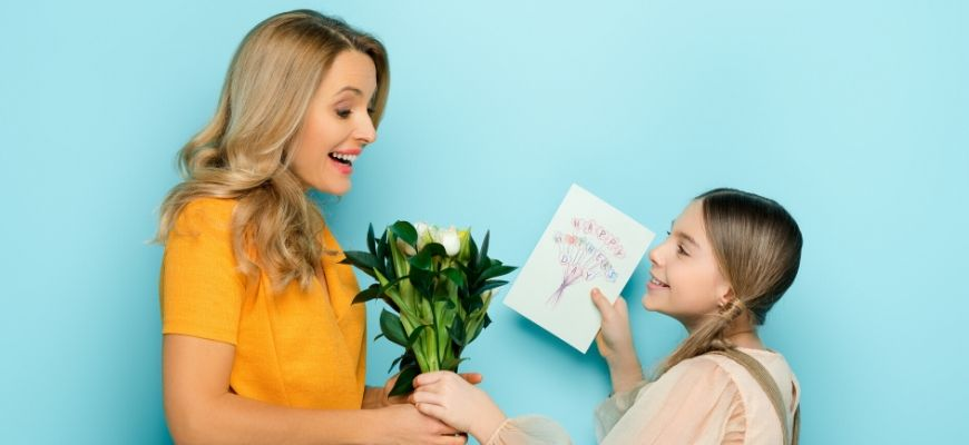 Daughter give her mother a flower bouquet and greeting card.