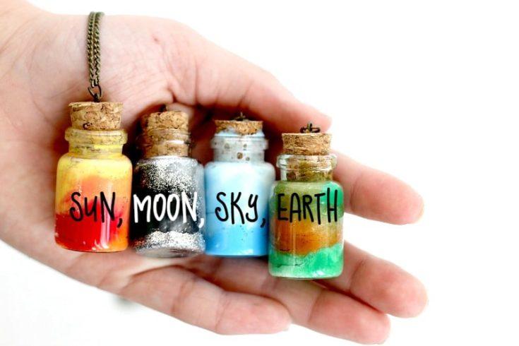 a hand holding four Element Jar Friendship Necklaces