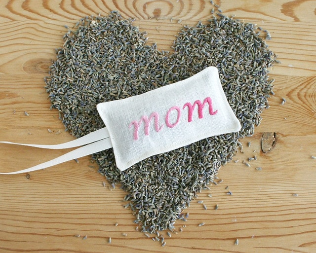 Embroidered lavender sachets for Mom on top of lavender seeds in arrange in a heart shape.