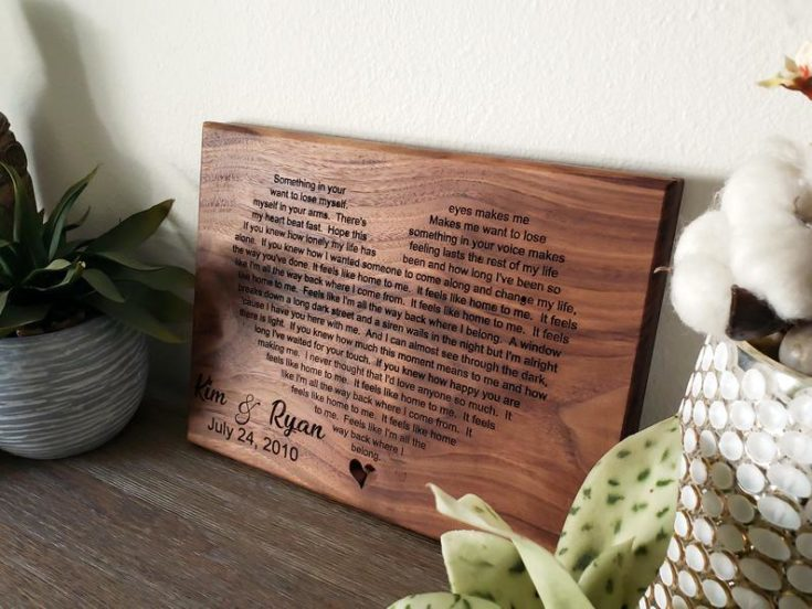 Couple's first dance lyrics engraved to a wooden plank and carved in heart shape.
