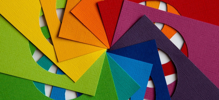Different colors of linen papers with a big whole and entertwined into a circular pattern.