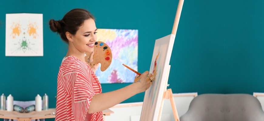 A smiling woman painting into the canvas