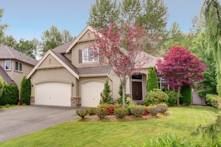 Lovely American home exterior with gray stucco, stone elements, attached garage and perfectly kept front yard.
