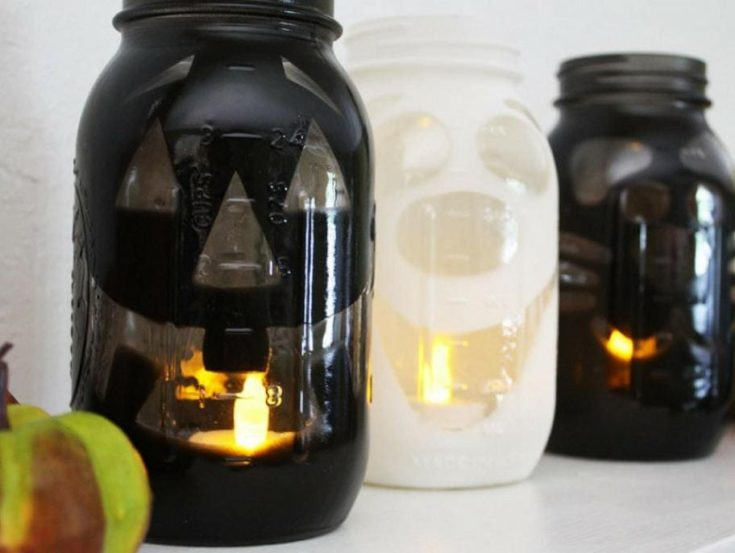 DIY Halloween luminaries sprayed black paints on the whole jar and putting stickers for the desired output of designs.