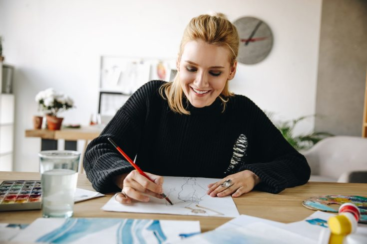A smiling fashion designer drawing sketch with a glass of water in the table