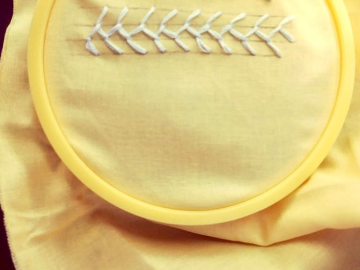 feather stitch embroidery example in a yellow cloth
