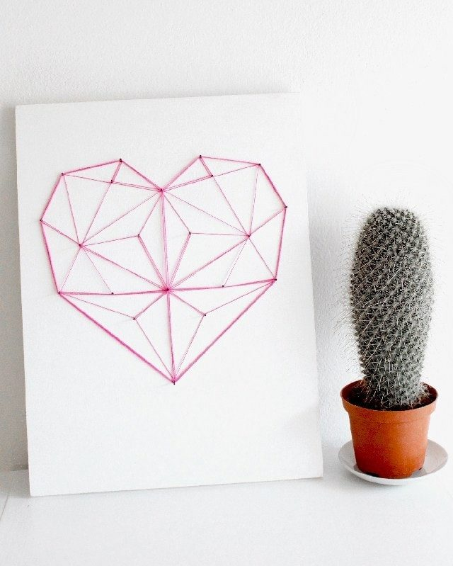 Geometrical heart red string art design on white plain board and potted cactus on his side.