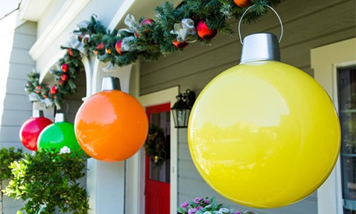 Yellow Orange Green Red giant Christmas balls hanging on porch