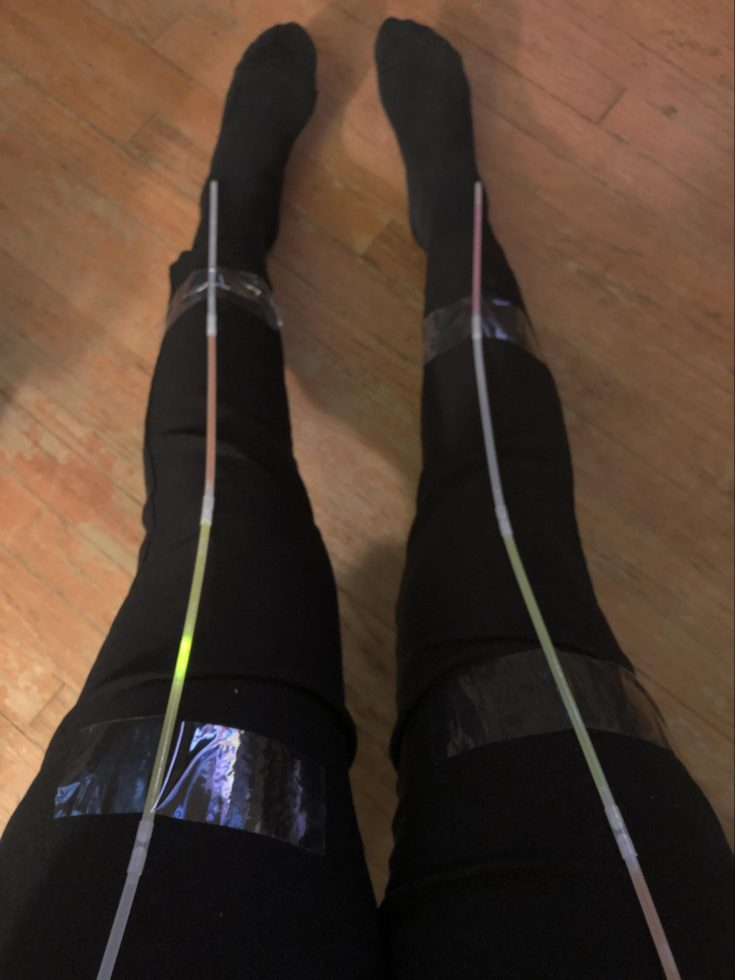 a close up shot of two legs of a person wearing black leggings with tube sticks on them