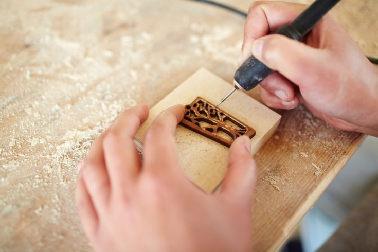 Hands of master of burning ornaments carving wooden board with pyrographic equipment