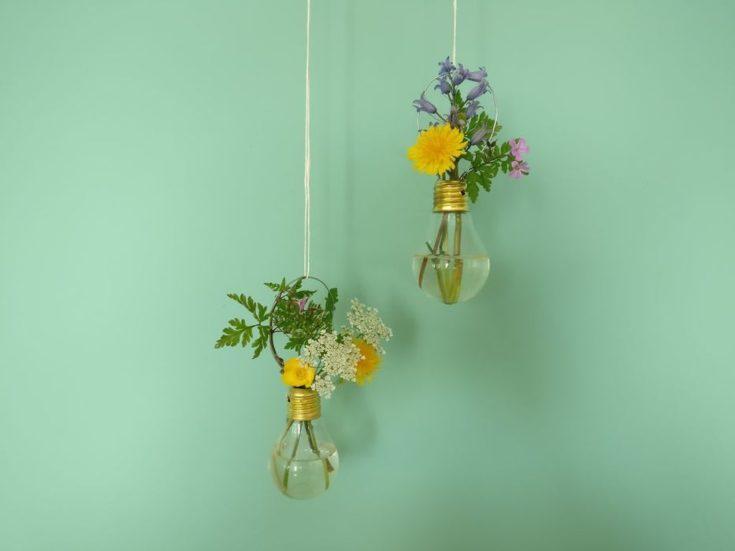Hanging lightbulb vases in mint green background.
